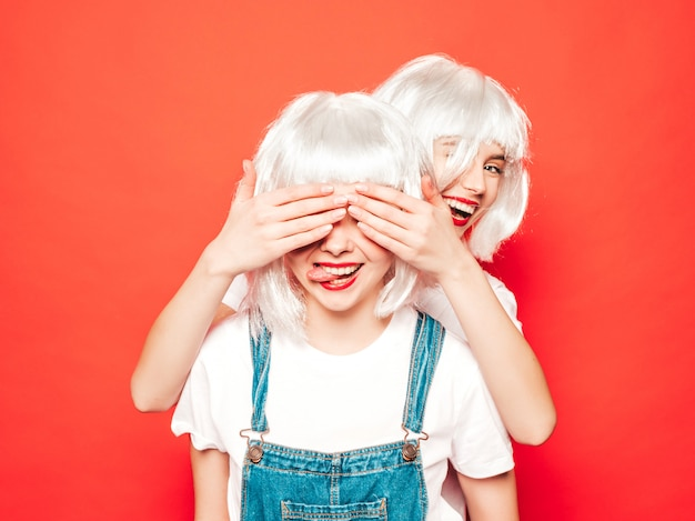 Two young sexy smiling hipster girls in white wigs and red lips.beautiful trendy women in summer clothes.models posing near red wall in studio.cover eyes with hands to her friend.surprise concept