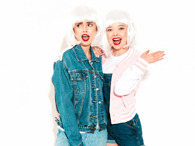 Two young sexy smiling hipster girls in white wigs and red lips going crazy