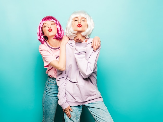 Two young sexy smiling hipster girls in wigs and red lips.beautiful trendy women in summer clothes.carefree models posing near blue wall in studio give air kiss