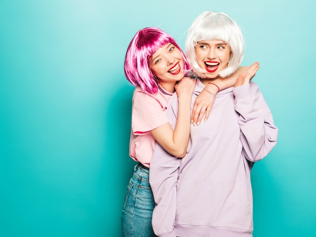 Two young sexy smiling hipster girls in wigs and red lips.beautiful trendy women in summer clothes.carefree models posing near blue wall in studio going crazy and hugging