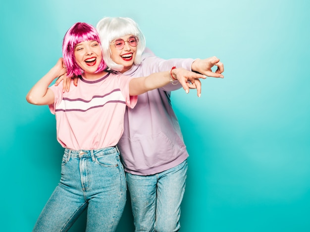 Two young sexy smiling hipster girls in wigs and red lips.beautiful trendy women in summer clothes.carefree models posing near blue wall in studio pointing on shop sales