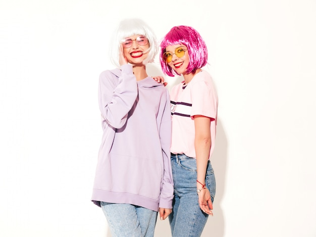 Two young sexy smiling hipster girls in wigs and red lips.beautiful trendy women in summer clothes.carefree models posing near white wall in studio going crazy and hugging