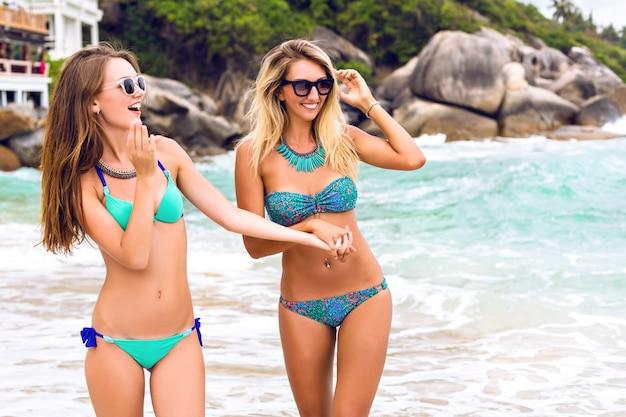 ゴシップを歩いて、楽園のビーチで楽しんでいる2人の若いセクシーな見事な女性。ビキニのファッション夏の肖像画の行く女の子は、エキゾチックな休暇を楽しんでいます。