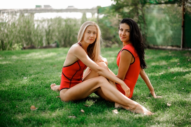 Two young sexy women dressed in swimsuits sitting on green grass
