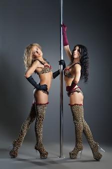 2人の若いセクシーな女性が暗い背景に対してポールダンスを行使します