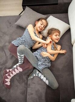ベッドで喧嘩する 2 人の若い姉妹