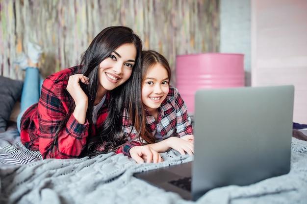 自宅のベッドルームで一緒に映画を見るためにラップトップを使用している10代の2人の若い姉妹。カメラに向かってポーズをとる