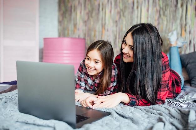 自宅のベッドルームで一緒に映画を見るためにラップトップを使用している10代の2人の若い姉妹