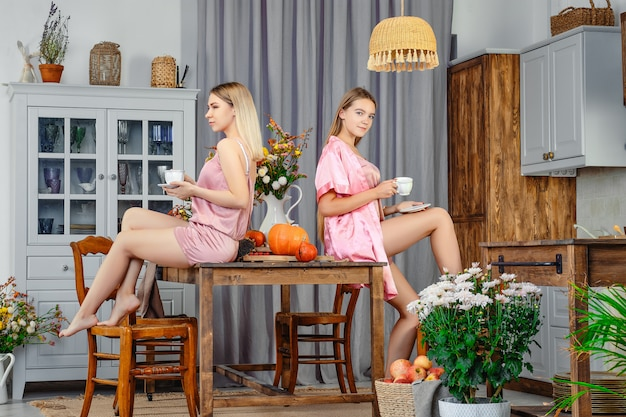 Two young sisters sitting back to back to each other in the kitchen