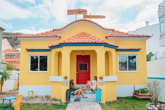 彼らの夏の家のポーチに座っている2人の若いスケーターの女性