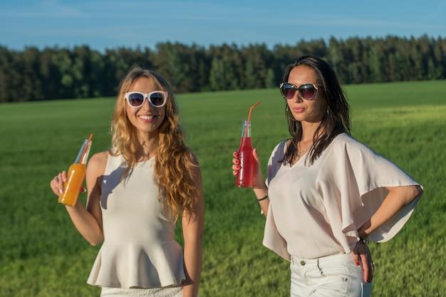 Две молодые стройные девушки в очках с вьющимися волосами улыбаются и пьют алкогольный или безалкогольный коктейль через соломинку из бутылки в солнечный летний день улыбается