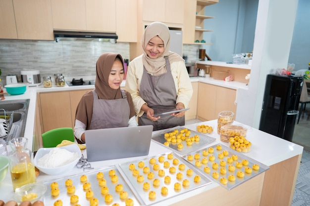 Two young small muslim business owner selling homemade nastar cake from home. muslim woman baking pineapple tart together
