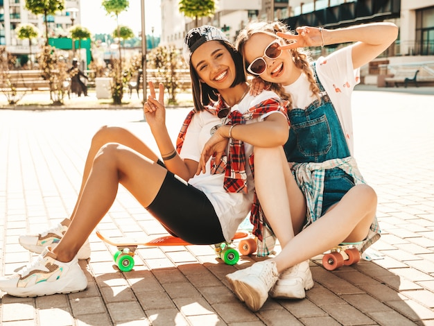 Two young smiling beautiful girls with colorful penny skateboards. women in summer hipster clothes sitting in the street background. positive models having fun and going crazy. showing peace sign