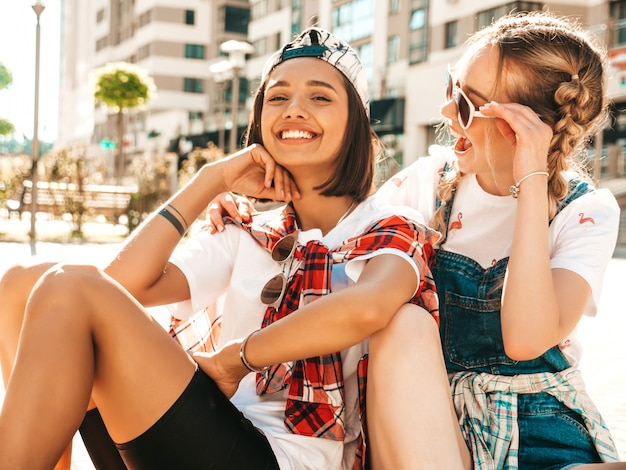 Two young smiling beautiful girls with colorful penny skateboards. women in summer hipster clothes sitting in the street background. positive models having fun and going crazy