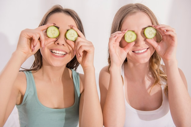 Two young smiling girlfriend putting on eyes cucumber.