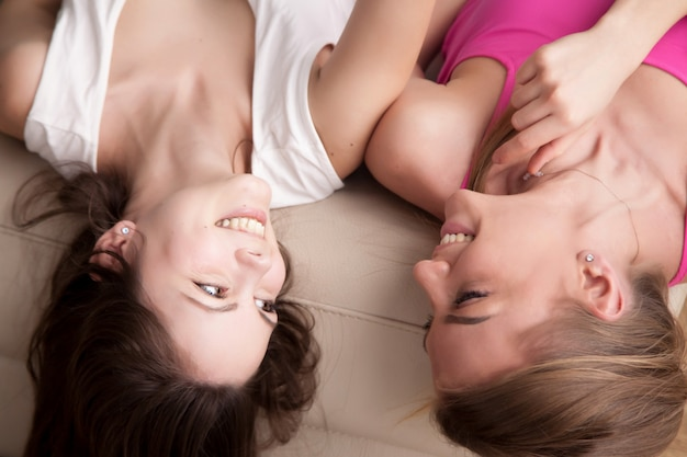 Two young smiling girlfriends lying on sofa and chatting.
