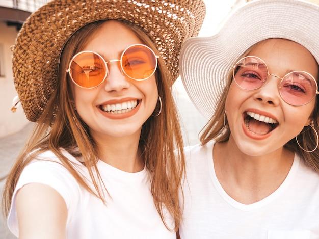 여름 흰색 티셔츠 옷에 두 젊은 미소 hipster 금발 여자. 스마트 폰에서 셀카 자기 초상화 사진을 찍는 여자. .