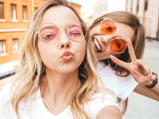 Two young smiling hipster blond women in summer clothes. girls taking selfie self portrait photos on smartphone. .
