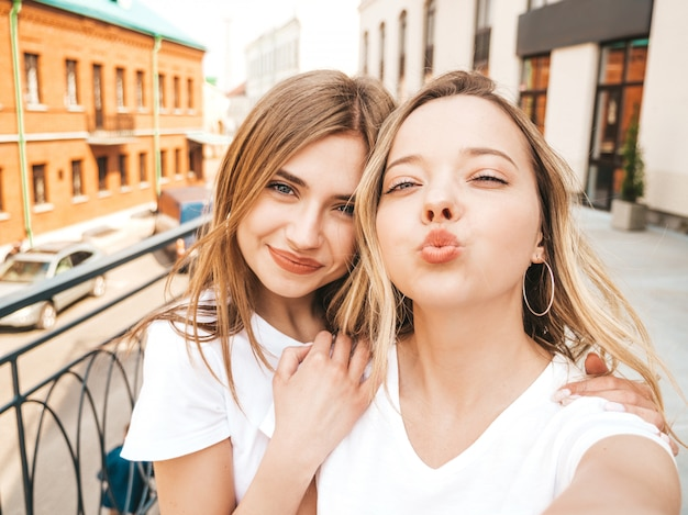 Two young smiling hipster blond women in summer white t-shirt clothes. girls taking selfie self portrait photos on smartphone.  .female making duck face