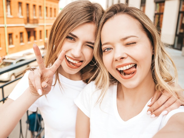 Two young smiling hipster blond women in summer white t-shirt clothes. girls taking selfie self portrait photos on smartphone.  .female shows peace sign and tongue