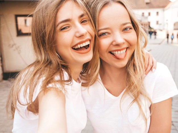 Two young smiling hipster blond women in summer white t-shirt clothes. girls taking selfie self portrait photos on smartphone.models posing on street background.female shows tongue
