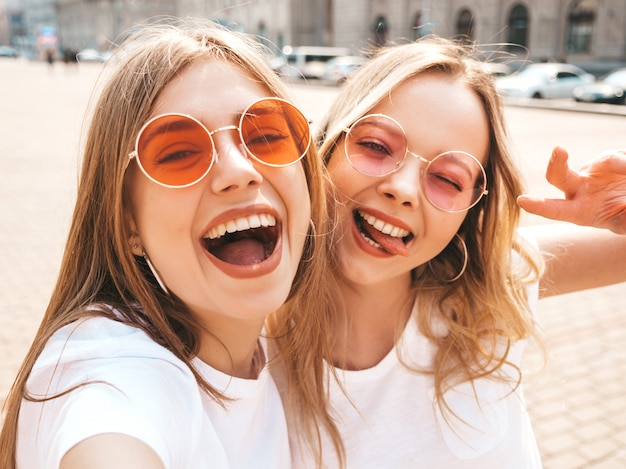 Two young smiling hipster blond women in summer white t-shirt clothes. girls taking selfie self portrait photos on smartphone.models posing on street  .female shows peace sign and tongue