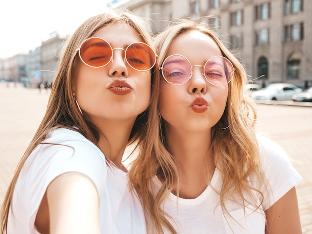 Two young smiling hipster blond women in summer white t-shirt clothes. girls taking selfie self portrait photos on smartphone.models posing on street  .positive female making duck face
