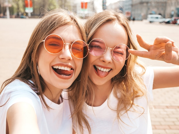 Two young smiling hipster blond women in summer white t-shirt clothes. girls taking selfie self portrait photos on smartphone.models posing on street  .positive female showing their tongue