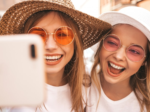 Two young smiling hipster blond women in summer white t-shirt clothes. girls taking selfie self portrait photos on smartphone.