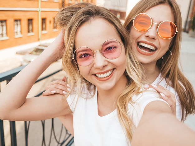Two young smiling hipster blond women in summer white t-shirt clothes. girls taking selfie self portrait photos on smartphone.  .