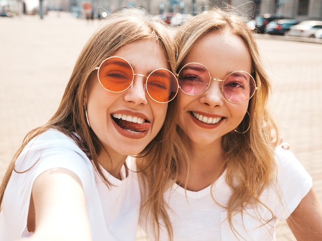Two young smiling hipster blond women in summer white t-shirt clothes.