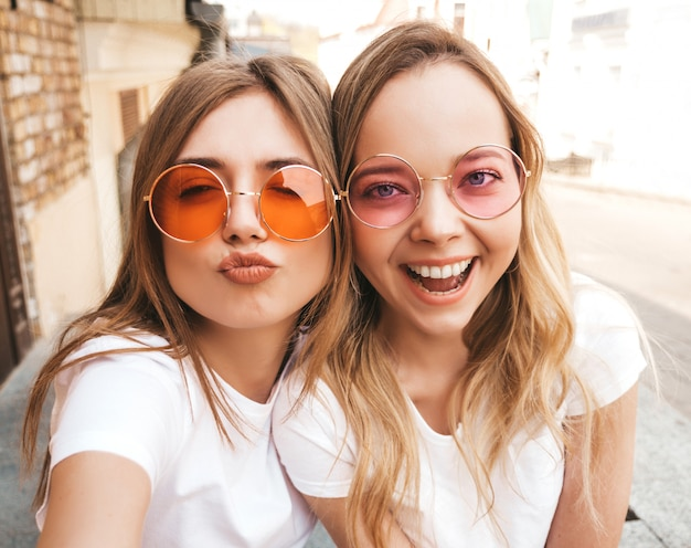 Two young smiling hipster blond women in summer white t-shirt. girls taking selfie self portrait photos on smartphone.  .female making duck face