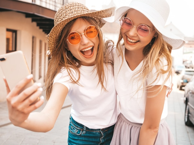 Two young smiling hipster blond women in summer white t-shirt. girls taking selfie self portrait photos on smartphone.models posing on street background.female shows positive emotions