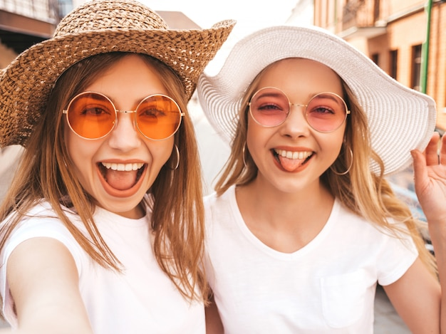 Two young smiling hipster blond women in summer white t-shirt. girls taking selfie self portrait photos on smartphone.models posing on street background.female shows tongue and positive emotions