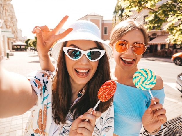 Two young smiling hipster women in casual summer clothes.