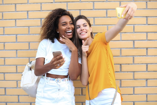 Две молодые улыбающиеся хипстерские женщины в летней одежде, позирует на улице. женщина, показывающая положительные эмоции лица.