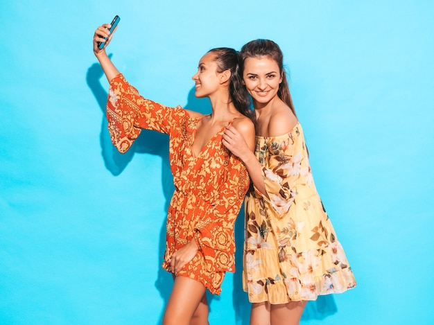 Две молодые улыбающиеся женщины-хипстеры в летних платьях хиппи