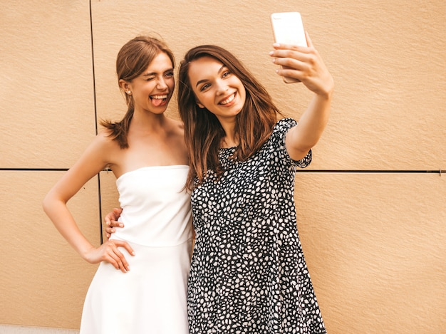 Two young smiling hipster women in summer clothes.