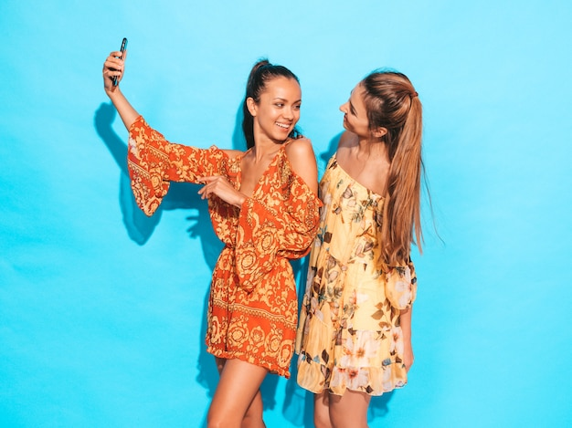 Two young smiling hipster women in summer hippie dresses.girls taking selfie self portrait photos on smartphone.models posing near blue wall in studio.female showing positive face emotions