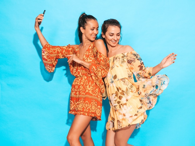 Two young smiling hipster women in summer hippie flying dresses.girls taking selfie self portrait photos on smartphone.models posing near blue wall in studio.female showing positive face emotions