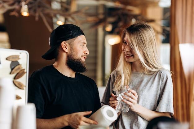 Два молодых улыбающихся человека, блондинка и мужчина с бородой, одетые в повседневную одежду, стоят рядом и смотрят друг на друга в уютной кофейне. .