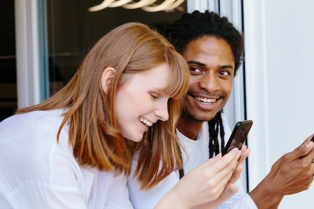 Two young smiling people leaning on a window using the mobile phone