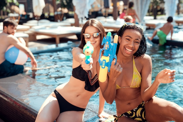Two young smiling women in bikini at poolside