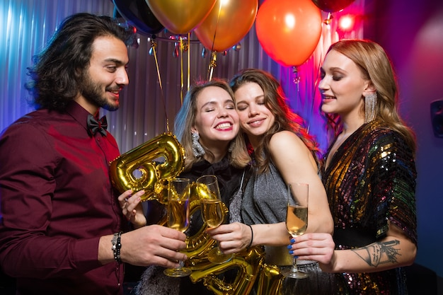 Two young smiling women clinking flutes of champagne with elegant man while enjoying birthday party in the night club