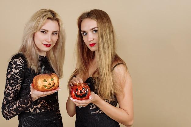ベージュの背景にハロウィーンのカボチャを保持している2人の若い笑顔の女性