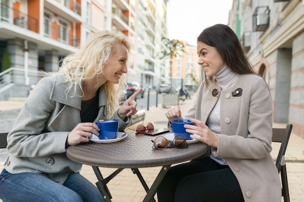 Two young smiling women in an outdoor cafe, drinking coffee
