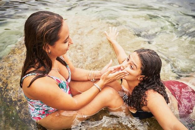 해변에서 놀고 조롱하는 두 젊은 스페인 여성