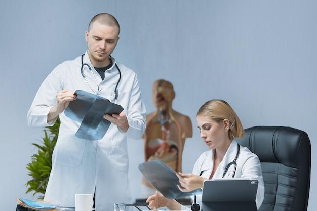 2人の若い専門医が明るいオフィスでx線について注意深く話し合っています。