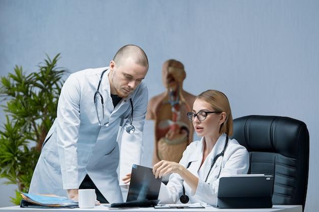 2人の若い専門医が患者のx線検査の結果について話し合う