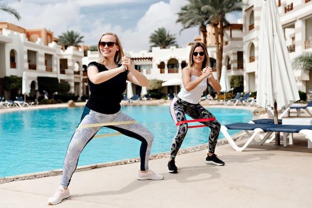 Две молодые спортивные девушки делают упражнения с резинкой